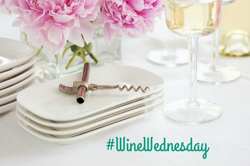 White wine, corkscrew, dishes and flowers, on a white tablecloth.