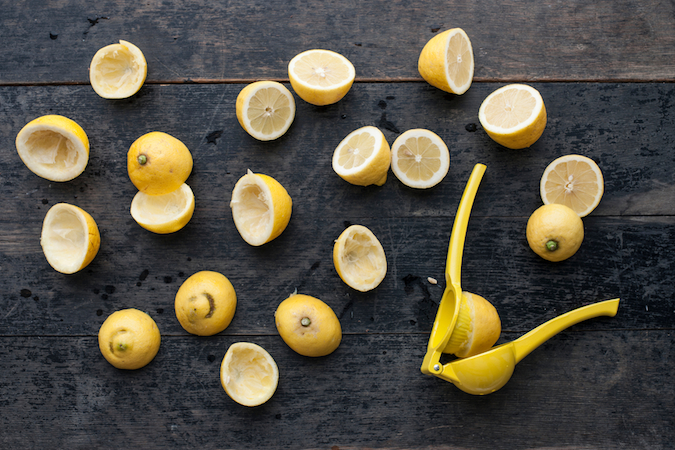 Food: Halved and partly squeezed lemons with yellow citrus squeezer